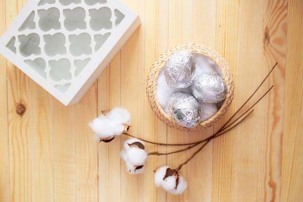 Huevos de pascua en mesa de madera blanca. flores y dulces alrededor.