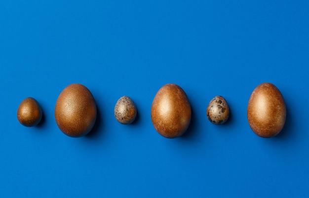Huevos de pascua modernos dorados aislados en azul