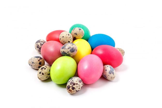 Los huevos de pascua multicolores se encuentran sobre un fondo blanco. huevos amarillos, rojos, verdes, azules y huevos de codorniz doblados juntos en una pila. celebración del concepto de pascua