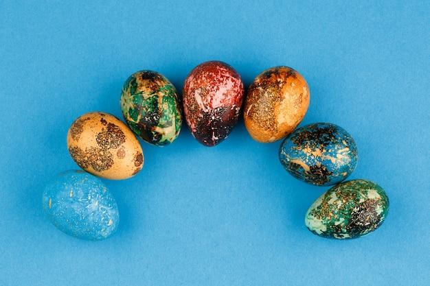 Los huevos de pascua multicolores rojos, verdes, azules, amarillos se presentan en semicírculo. huevos de pascua pintados sobre un fondo azul. copia espacio