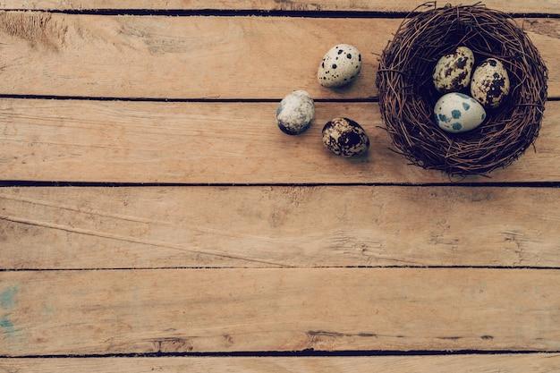 Huevos de pascua y nido en mesa de madera y fondo con espacio de copia