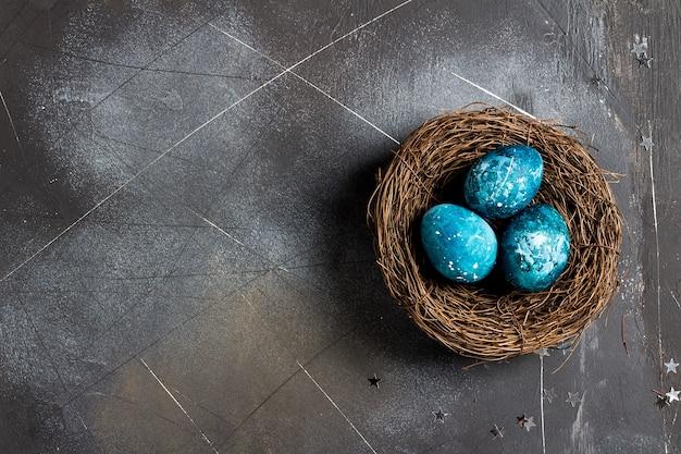 Huevos de pascua en nido pintados a mano en azul.