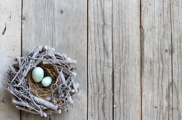 Huevos de pascua en el nido en la vista superior de la mesa de madera gris con espacio de copia
