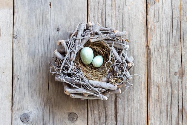 Huevos de pascua en el nido en la vista superior de la mesa de madera gris