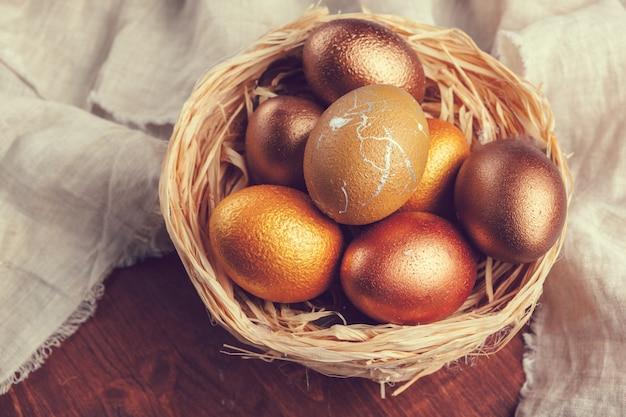 Huevos de pascua oro en mesa de madera