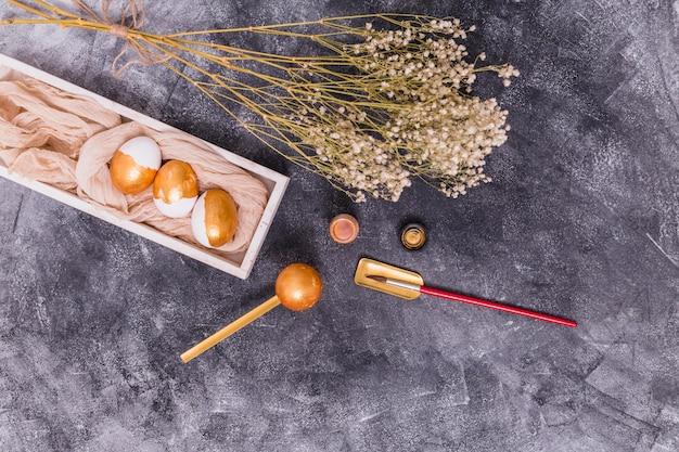 Huevos de pascua de oro con pincel y flores