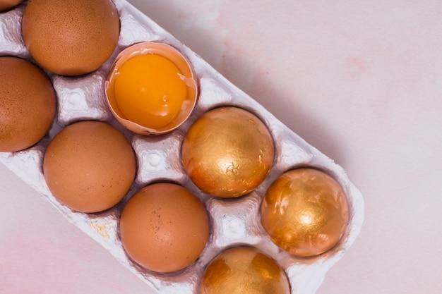 Huevos de pascua de oro en la rejilla en la mesa de luz