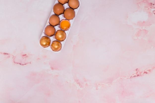 Huevos de pascua de oro en la rejilla en la mesa