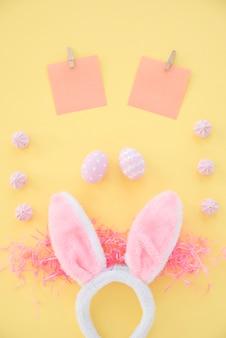 Huevos de pascua con papeles en blanco y orejas de conejo en mesa