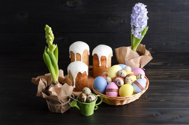 Huevos de pascua, pastel de pascua y jacintos sobre un fondo oscuro