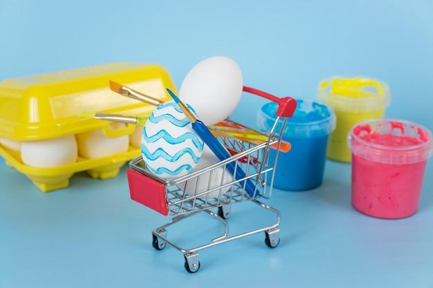 Huevos de pascua y pinceles en carrito de compras con pinturas y bandeja de huevos sobre fondo azul.