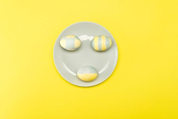 Huevos de pascua pintados de amarillo-gris en una placa gris sobre una superficie amarilla