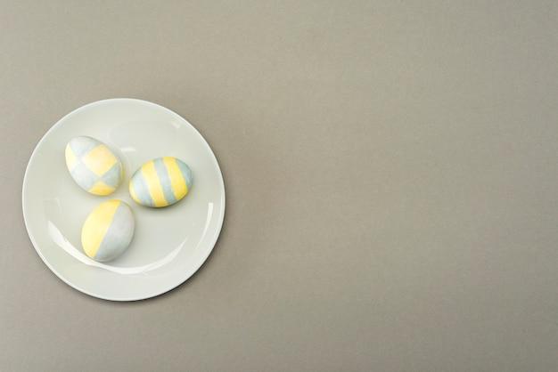 Huevos de pascua pintados de amarillo-gris en una placa gris sobre una superficie gris con lugar para texto