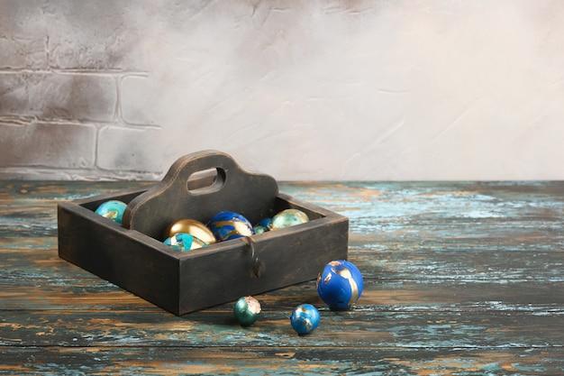Huevos de pascua pintados de colores en caja de madera oscura