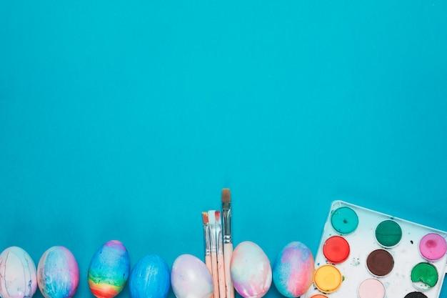 Huevos de pascua pintados; cuadro de pinceles y pinturas al agua en el fondo azul con espacio de copia