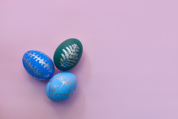 Huevos de pascua pintados en la opinión superior del fondo rosado. aplanada con espacio de copia
