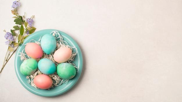 Huevos de pascua en un plato cerca de ramitas de flores