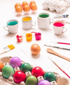 Huevos de pascua en un recipiente cerca de pinceles y tinte líquido en tazas