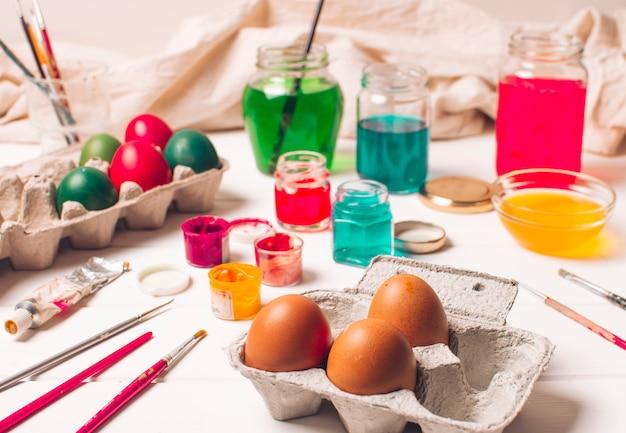 Huevos de pascua en recipientes cerca de cepillos y tinte líquido en latas
