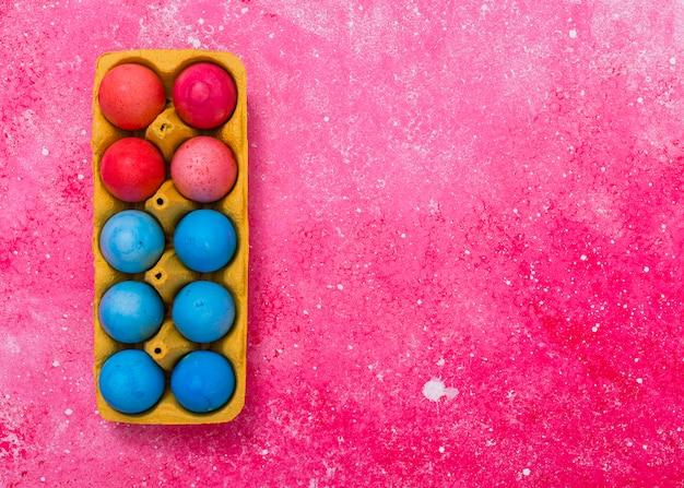 Huevos de pascua en rejilla en mesa rosa