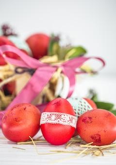 Huevos de pascua rojos atados con cinta de encaje de cerca, acostado en una canasta de pascua con un lazo, bodegón