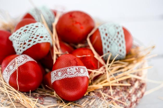 Huevos de pascua rojos en un nido de heno, atado una cinta de encaje, de cerca, acostado sobre una madera blanca