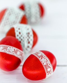 Huevos de pascua rojos sobre un blanco atado con una cinta de encaje, primer plano, acostado sobre una madera blanca