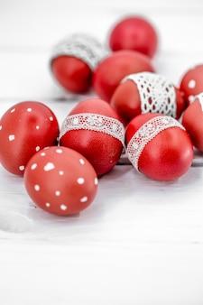 Huevos de pascua rojos sobre cinta blanca de encaje atado, close-up, acostado sobre una madera blanca