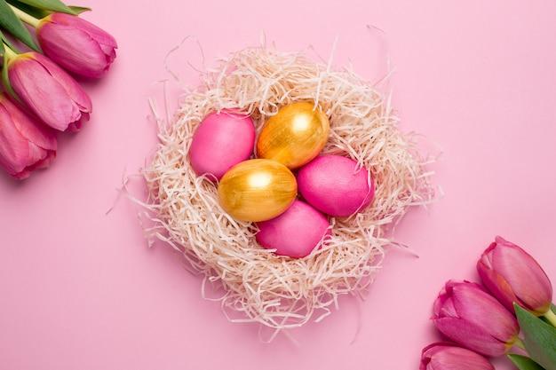 Huevos de pascua rosa y oro con flores sobre una superficie rosa