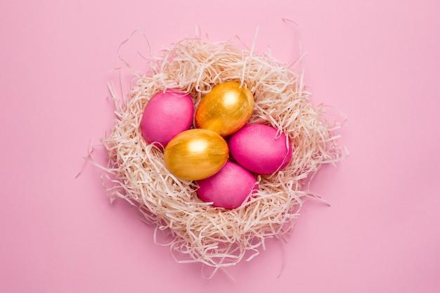 Huevos de pascua rosa y oro sobre una superficie rosa