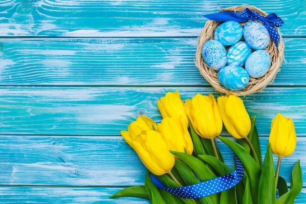 Huevos de pascua y tulipanes. decoración festiva sobre fondo de madera. tarjeta navideña con espacio de copia