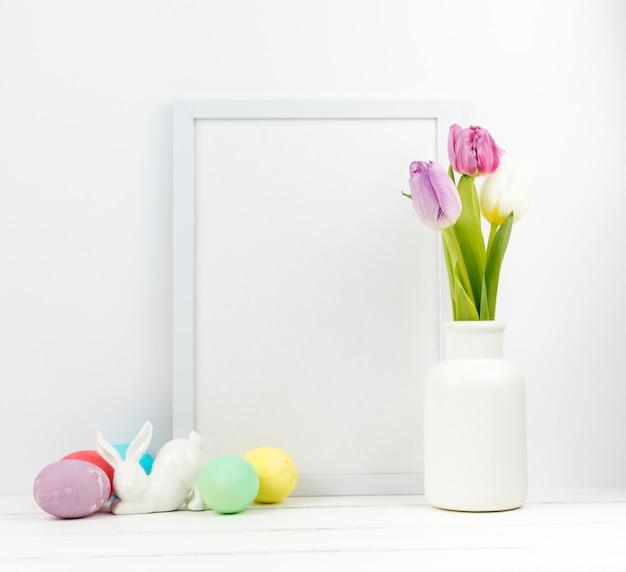 Huevos de pascua con tulipanes en florero y marco en blanco