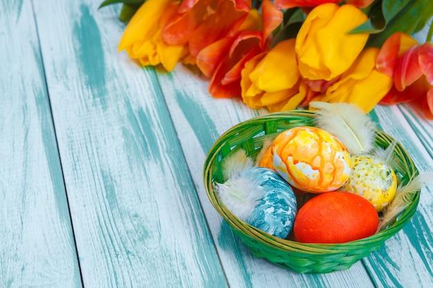 Huevos de pascua con tulipanes en madera azul