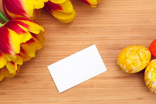 Huevos de pascua con los tulipanes en el tablero de madera, concepto del día de fiesta de pascua.