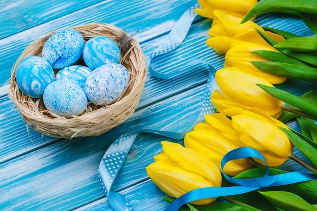 Huevos de pascua con tulipanes en tablero de madera, vacaciones de pascua. copyspace para texto