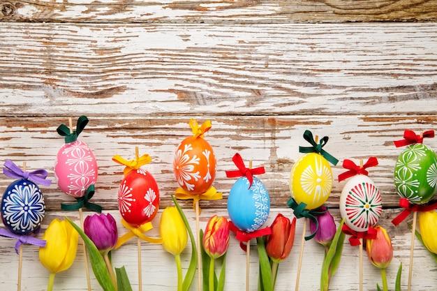 Huevos de pascua y tulipanes en tablones de madera