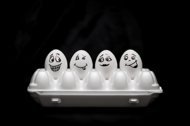Huevos pintados a mano reales. huevos blancos con caras dibujadas dispuestas en cartón.