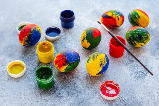 Huevos, pinturas y cepillo multicolores de pascua en una tabla. preparación para unas vacaciones.