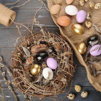 Huevos y plumas de colores pintados de diferentes tamaños para pascua