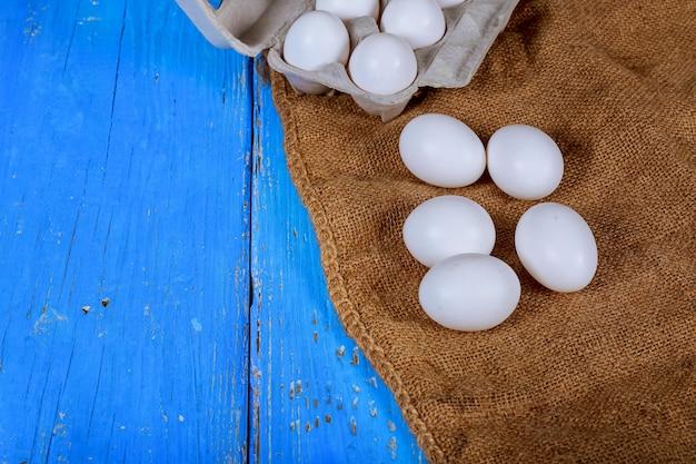 Huevos del pollo en una caja de cartón en una tabla de madera. cocina de yema de huevo