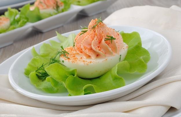Huevos rellenos de paté de salmón con pimiento rojo en hojas de lechuga