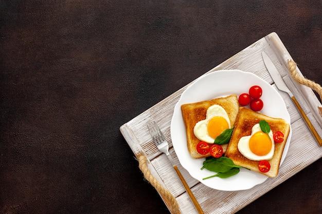Huevos revueltos en forma de corazón en un plato con tomates, verduras y café