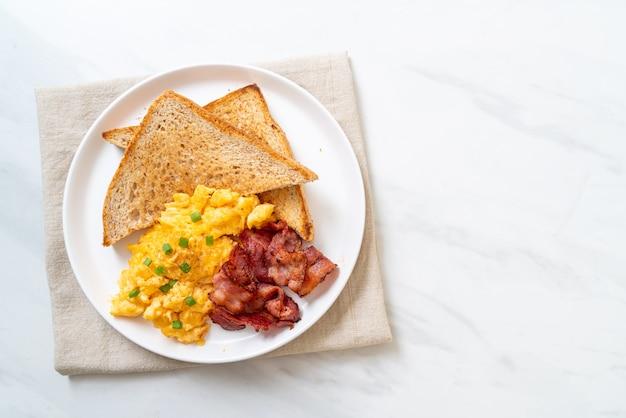 Huevos revueltos con pan tostado y tocino para el desayuno