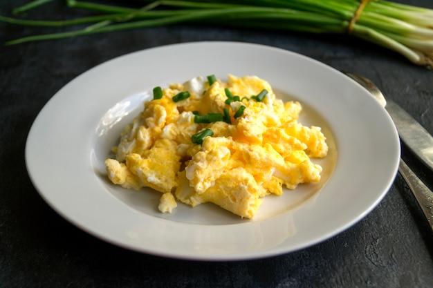 Huevos revueltos en un plato blanco. la vista desde la parte superior.