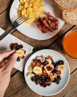 Huevos revueltos con tocino, jugo de naranja y frutas secas