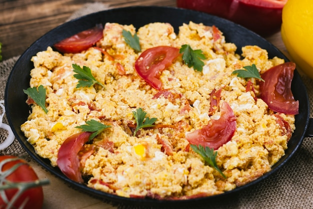 Huevos revueltos con tomate en una sartén