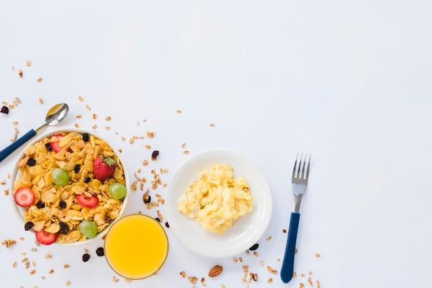 Huevos revueltos; vaso de jugo y copos de maíz con frutos secos sobre fondo blanco