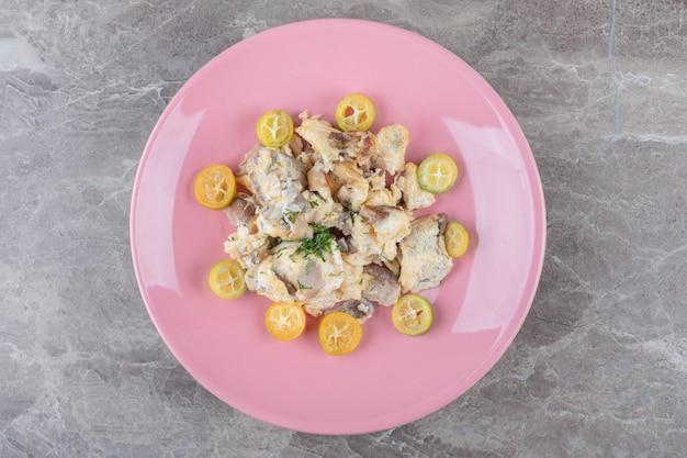 Huevos revueltos con verduras en plato rosa.