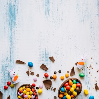 Huevos rotos con caramelos cerca de conejitos