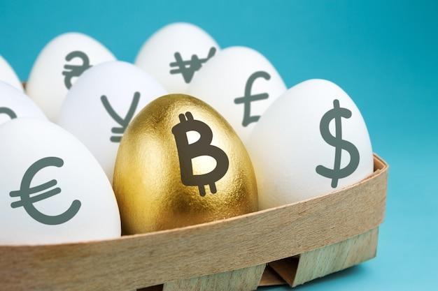 Huevos con signos de moneda en embalaje de madera y huevo de oro con un signo de bitcoin